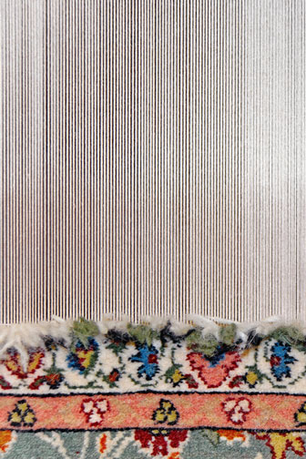traditional rug being woven on a vertical carpet loom